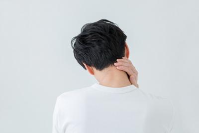 後ろを向き首をかしげて悩む男性のイメージ